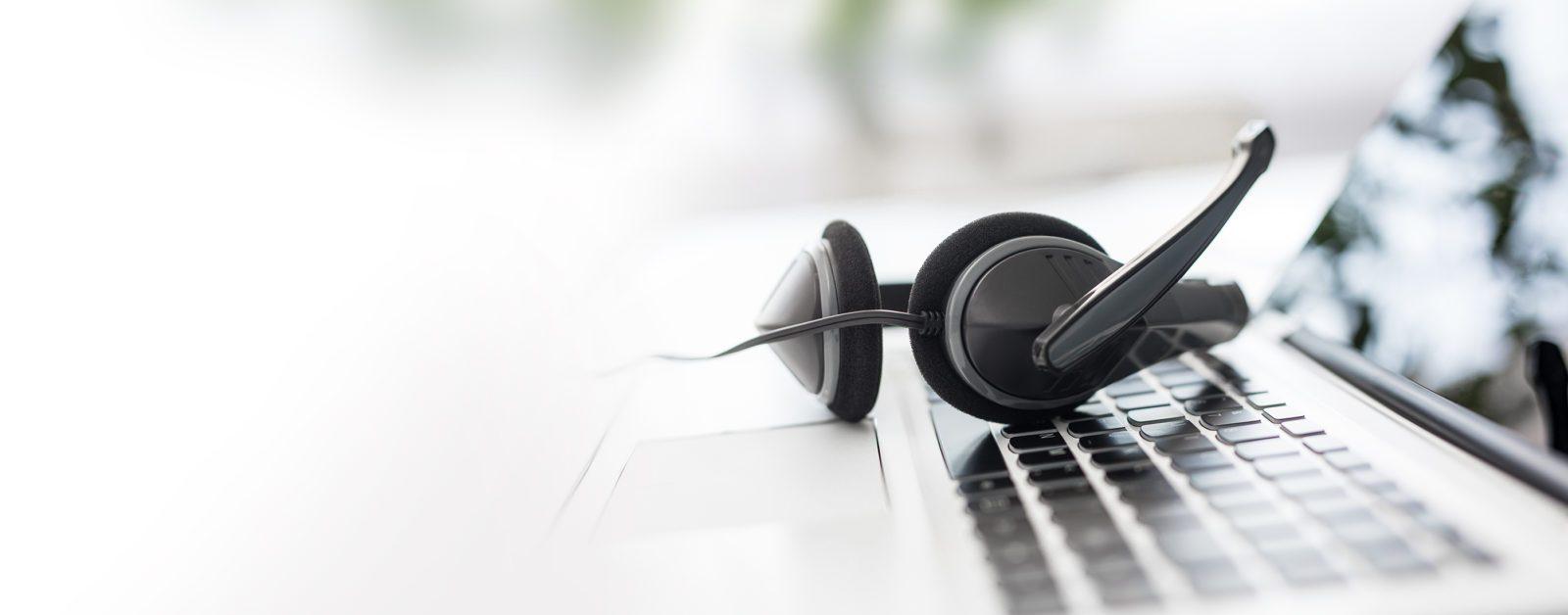 OWA Header Techberatung, Kopfhörer auf Laptop